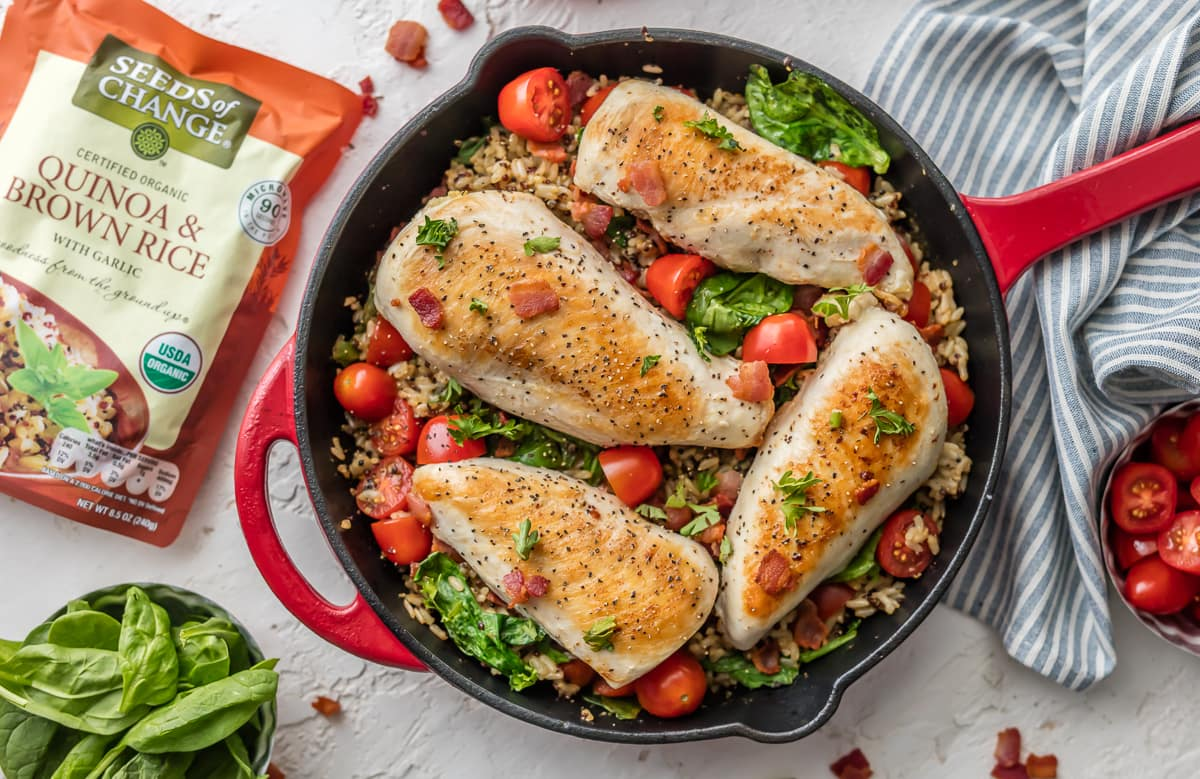 Red skillet filled with chicken breast, spinach, tomato, bacon, rice, and quinoa