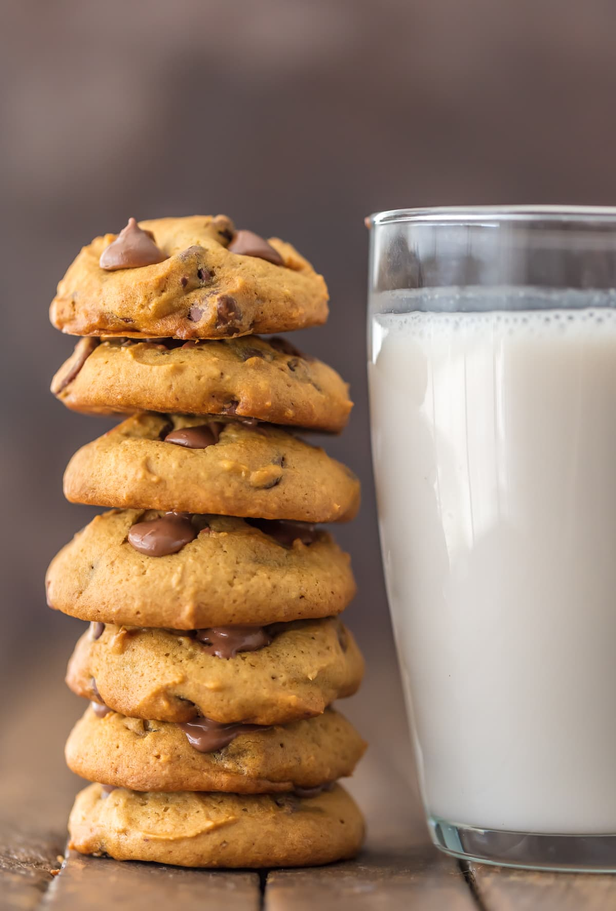 A stack of applesauce chocolate chip cookies next to a glass of milk