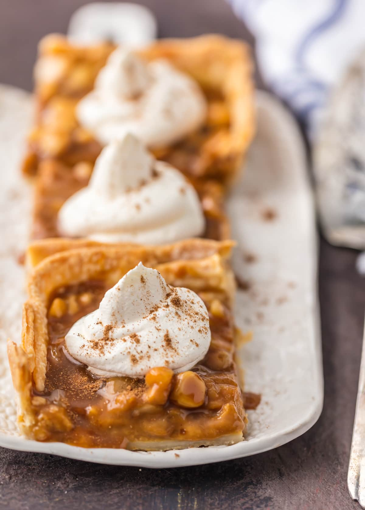 Pumpkin Pie bars lined up on a plate, topped with whipped cream