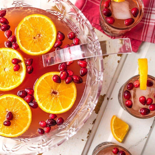 Holiday Punch is one of our favorite EASY PUNCH RECIPES perfect for Thanksgiving or Christmas! This Vodka punch is made with Cranberry Juice, Orange Juice, Ginger Ale, Sparkling Cider and more! You can pour in the Vodka or make it your new Non Alcoholic Christmas Punch Recipe. One of our very favorite Holiday Punch Recipes.