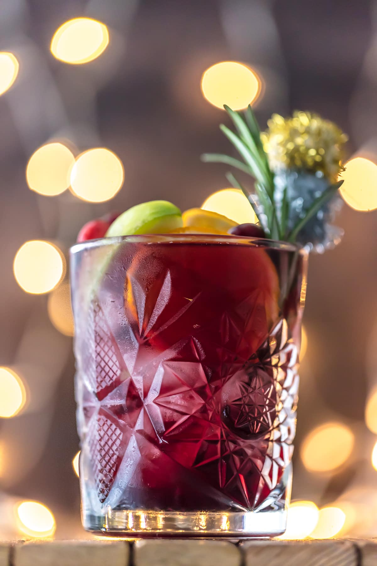 A glass of holiday sangria garnished with rosemary and fruit