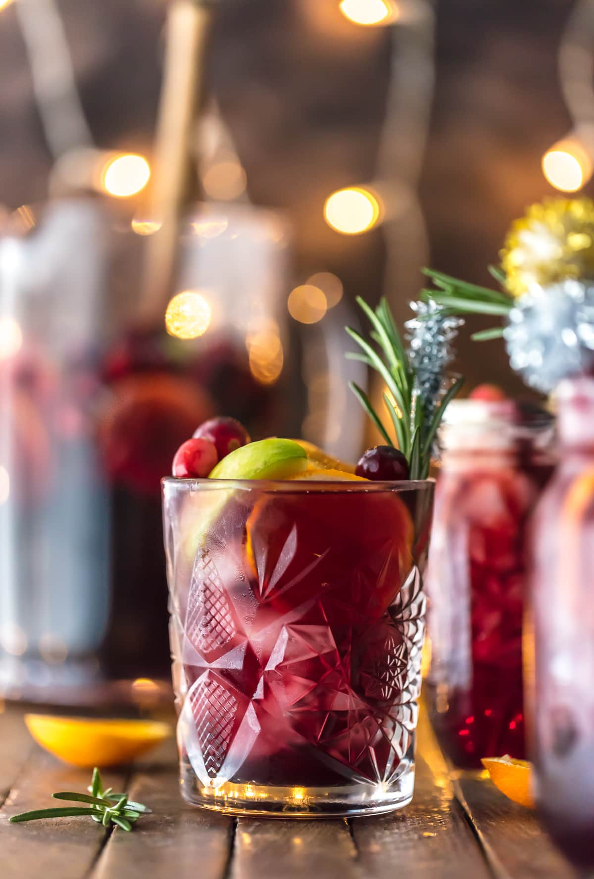 Easy Holiday Sangria recipe in a glass with rosemary and sliced fruit
