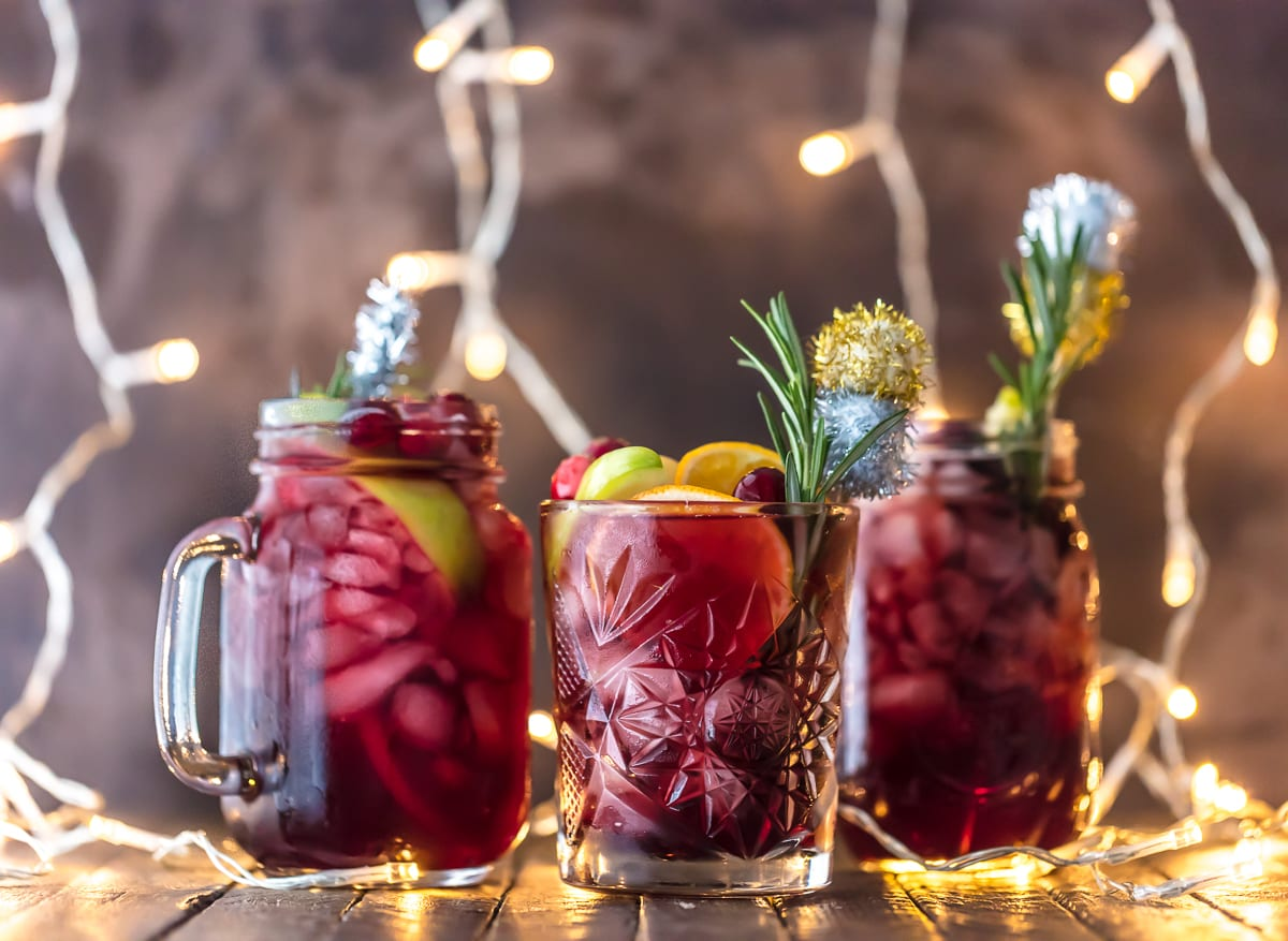 Three glasses of Christmas Sangria, garnished with rosemary and fruit
