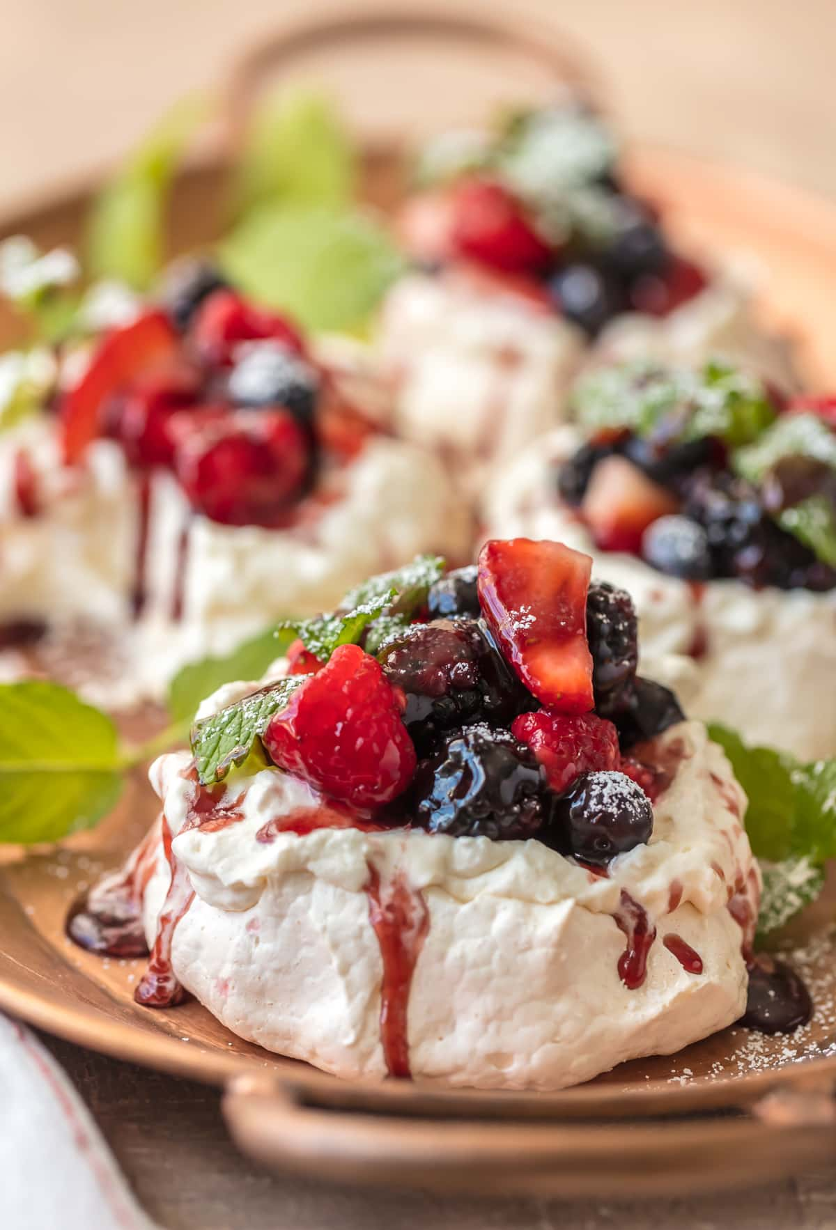 Mini Pavlova recipe topped with berries,sauce, and powdered sugar