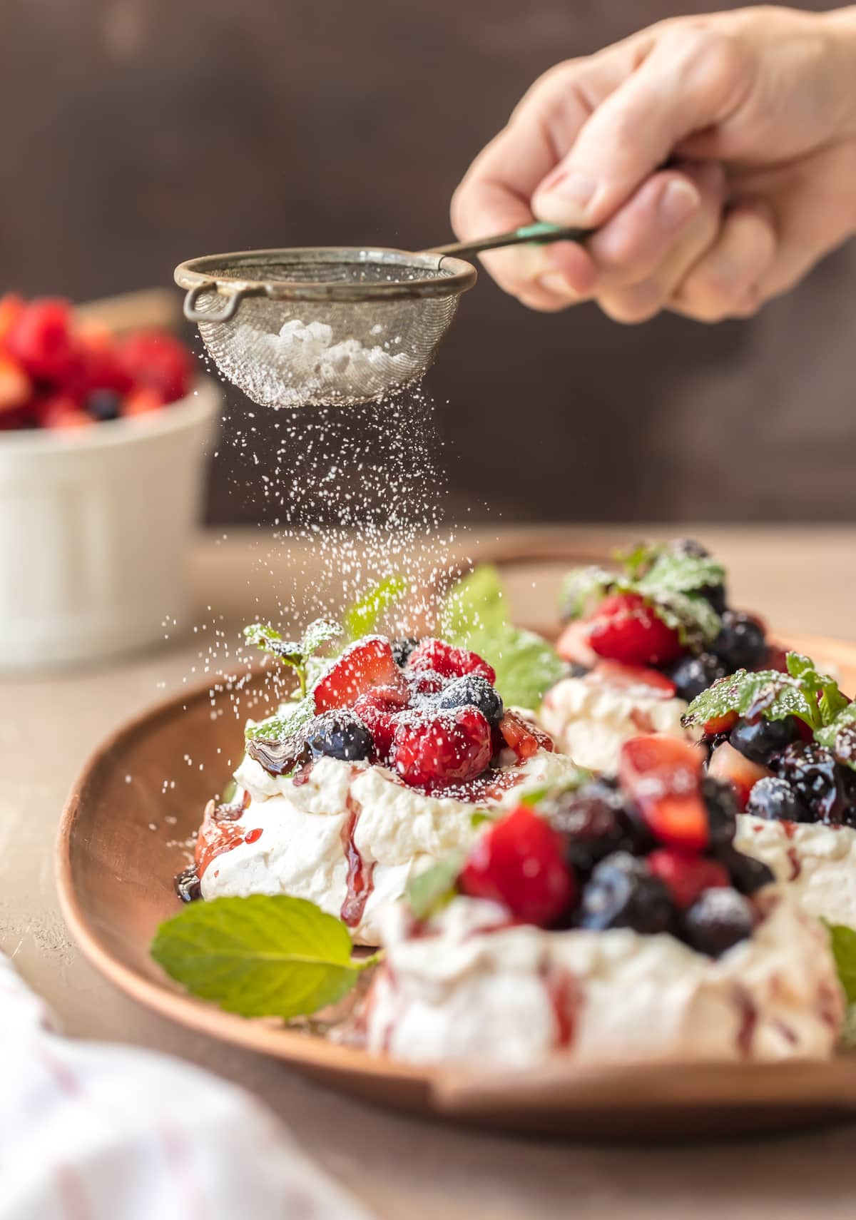 These MINI PAVLOVAS topped with fresh fruit, whipped cream, and fruit syrup is the ULTIMATE holiday dessert. The perfect dessert recipe for Christmas or any celebration. Beautiful, delicious, and EASY!