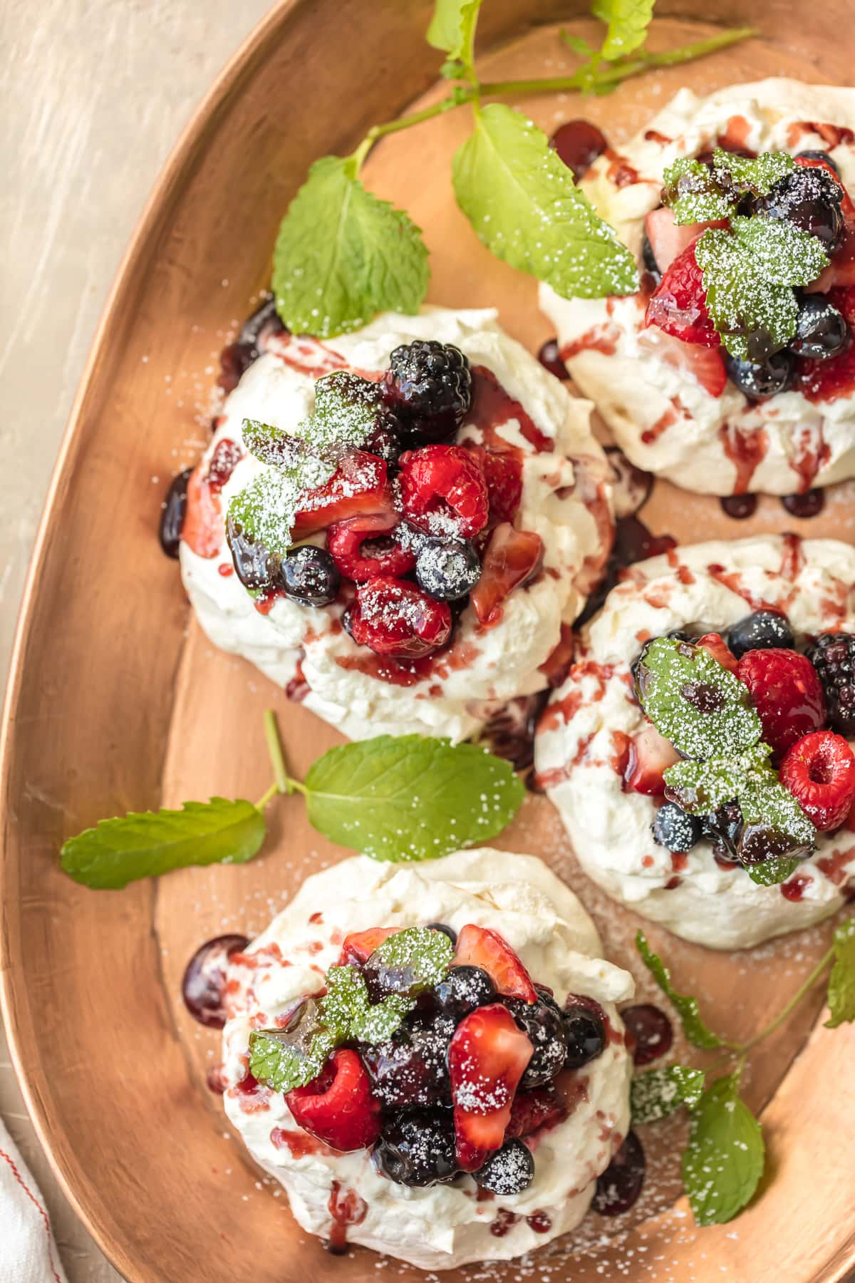 Mini Pavlovas - Meringue desserts topped with berries on a serving tray
