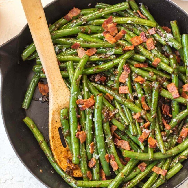 burbon green beans and bacon in skillet with wooden spoon