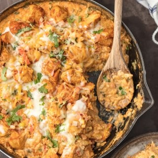 SKILLET CHICKEN CON QUESO is the ultimate one pot meal! Cheesy rice loaded with cilantro, pico de gallo, green chiles, and cream topped with taco spiced chicken. Comfort food has never been easier or cheesier!