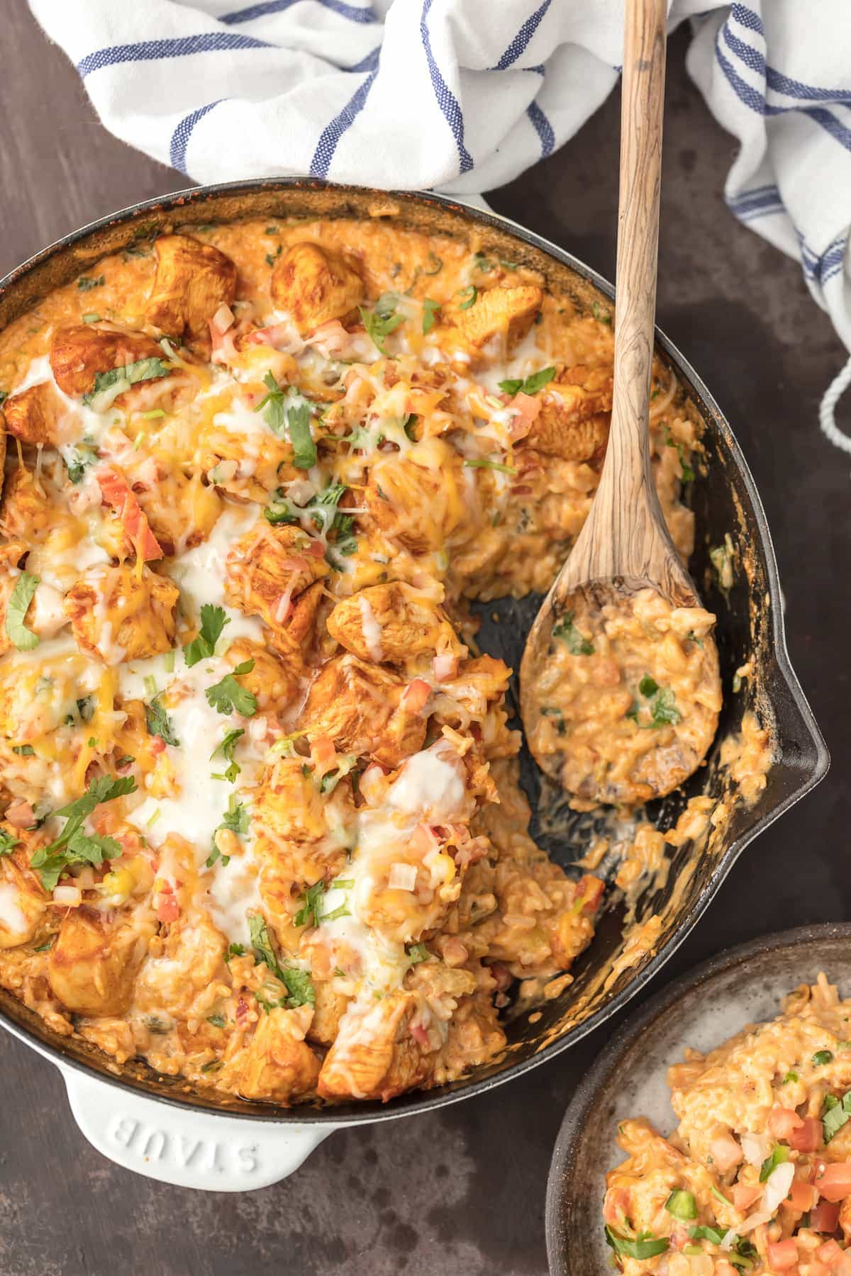 Chicken con Queso (Skillet Queso Chicken) is the ultimate one pot meal! Cheesy rice loaded with cilantro, pico de gallo, green chiles, and cream topped with taco spiced chicken. This one pan recipe is so cheesy, easy, and amazing. I used to always order Pollo con Queso at Mexican Restaurants and now I can easily make it at home. Chicken and Cheese...is there anything better?