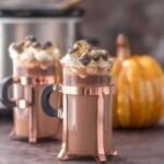 mugs of spiked hot chocolate in front of a pumpkin