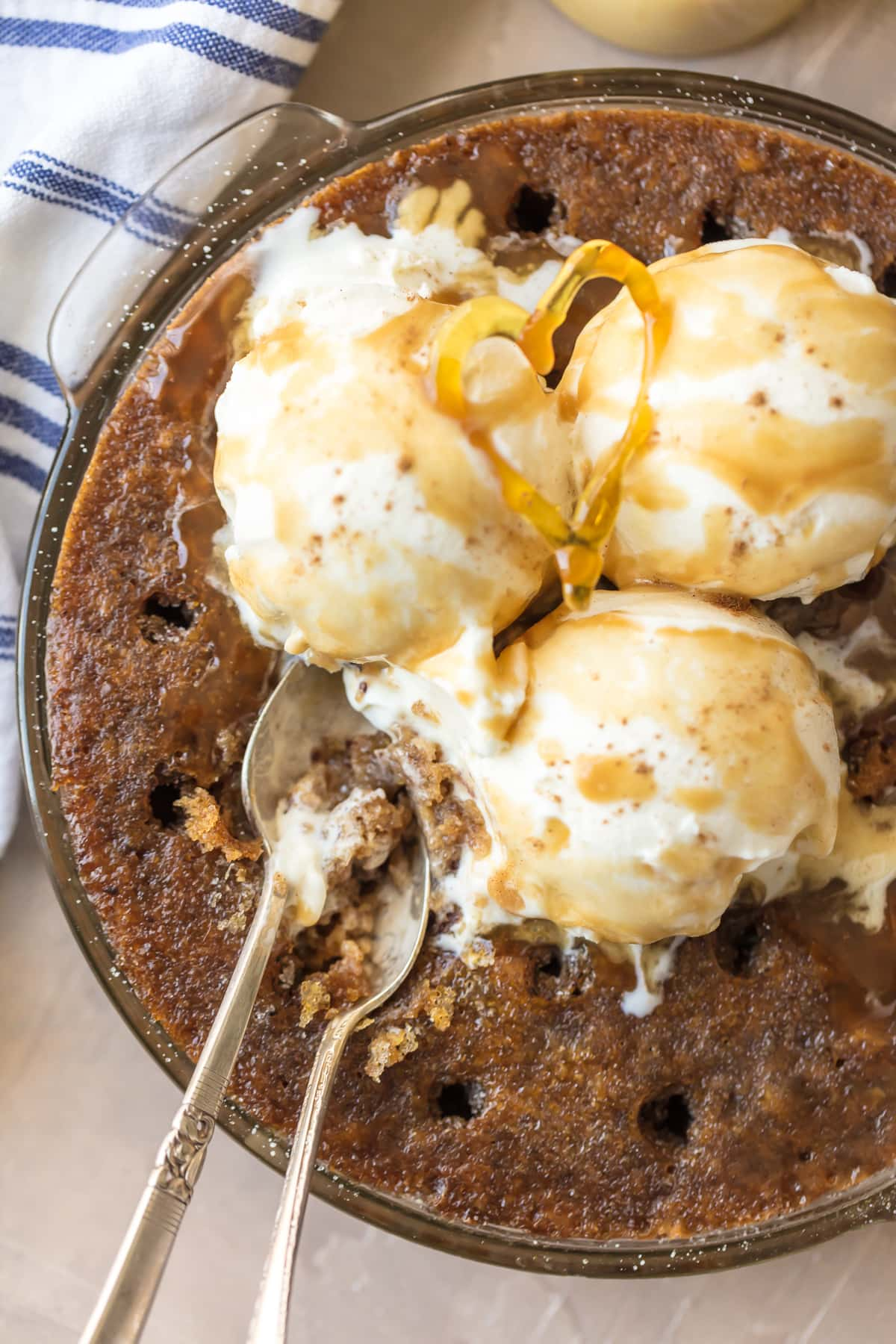 Toffee Pudding Poke Cake in a baking dish, topped with ice cream