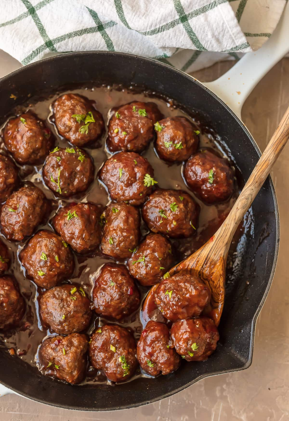 A skillet filled with cranberry cocktail meatballs