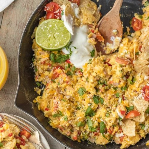 cheesy migas in skillet with wooden spoon