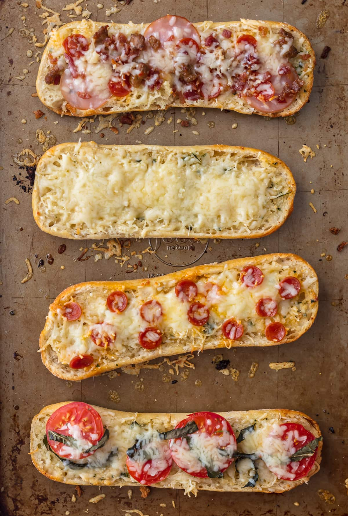 Four french bread pizza on a baking sheet: one topped with meat, one with cheese, one with pepperonis, one with tomatoes and basil