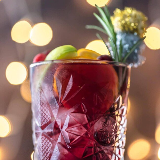 close up shot of holiday sangria with twinkling lights in the background