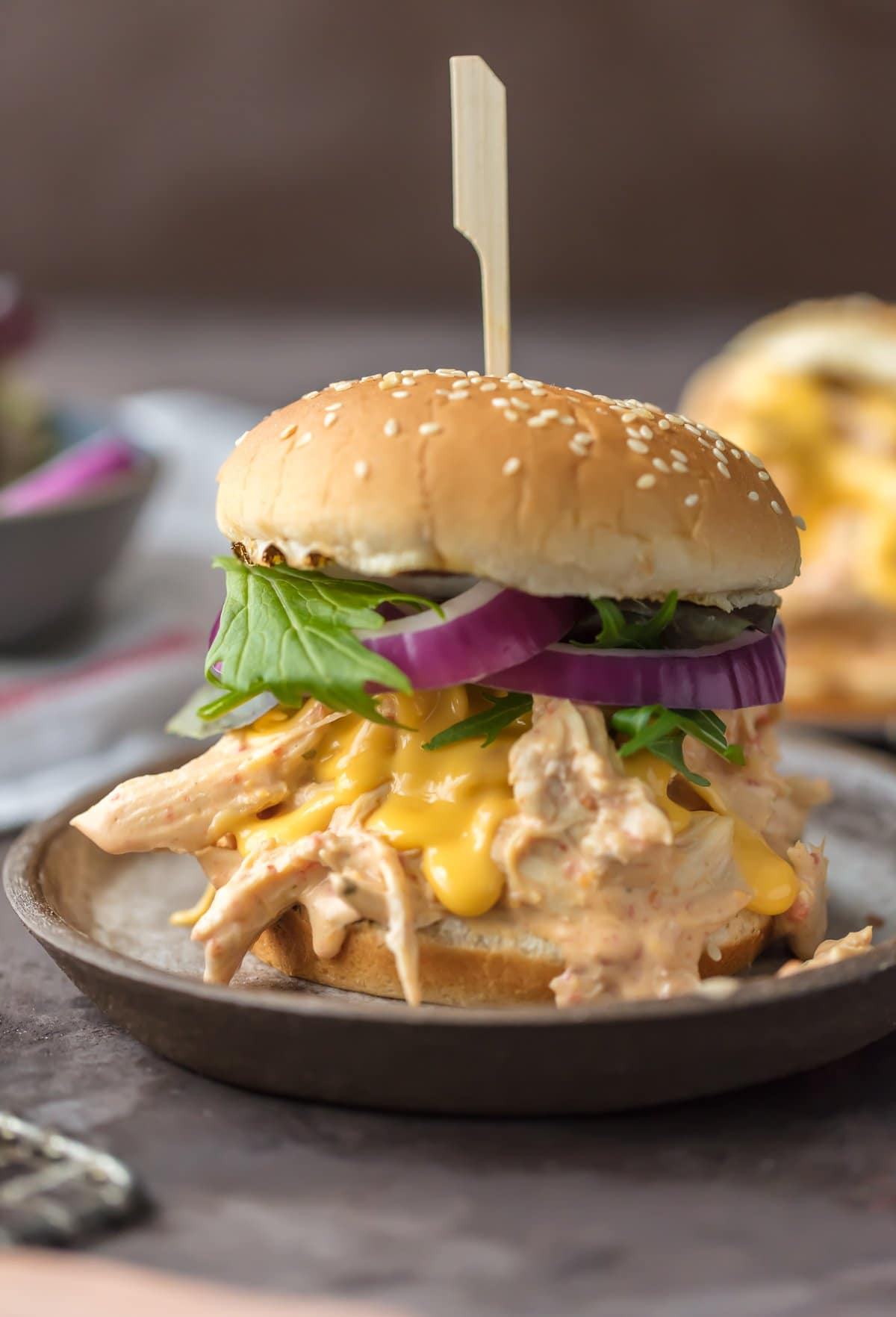 Slow Cooker Rotel Dip Chicken Sandwich, on a hamburger bun with lettuce and onion