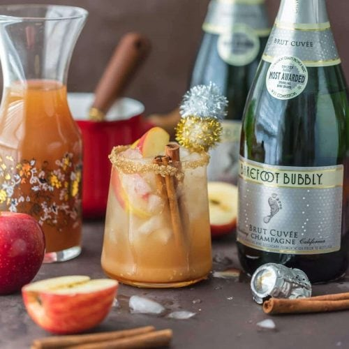 SPARKLING APPLE PIE ON THE ROCKS is the perfect Fall cocktail! Cinnamon Apple Cider mixed with Caramel Apple Simple Syrup and topped with bubbly champagne! BEST HOLIDAY DRINK EVER!