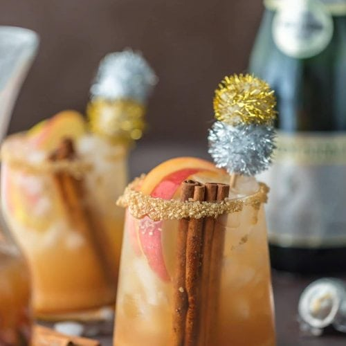 cocktails in glasses garnished with glitter pom poms
