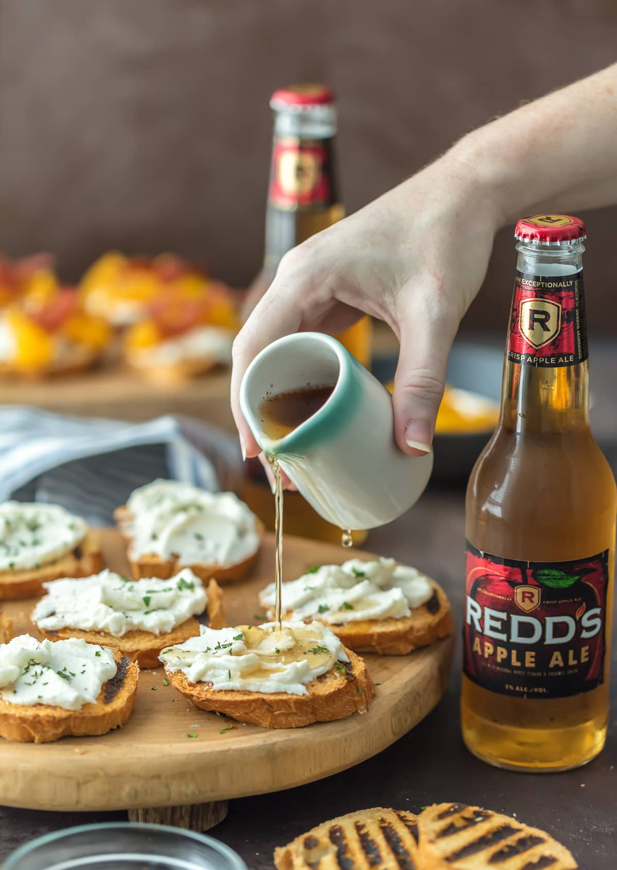 Goat Cheese Crostini on a wooden serving platter, with two Redd's Apple Ales