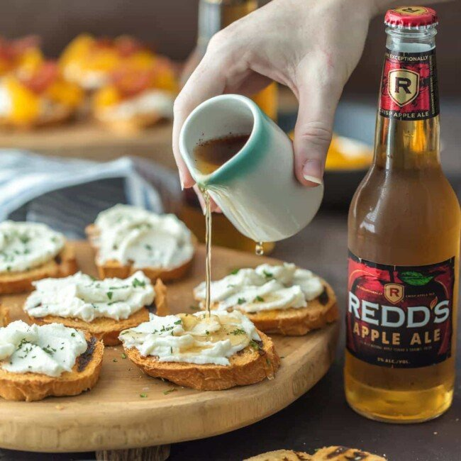whipped goat cheese bruschetta with honey being poured