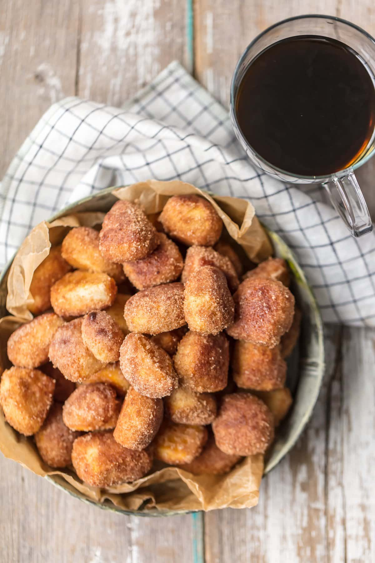 A basket of cinnamon sugar biscuit bites next to a cup of coffee