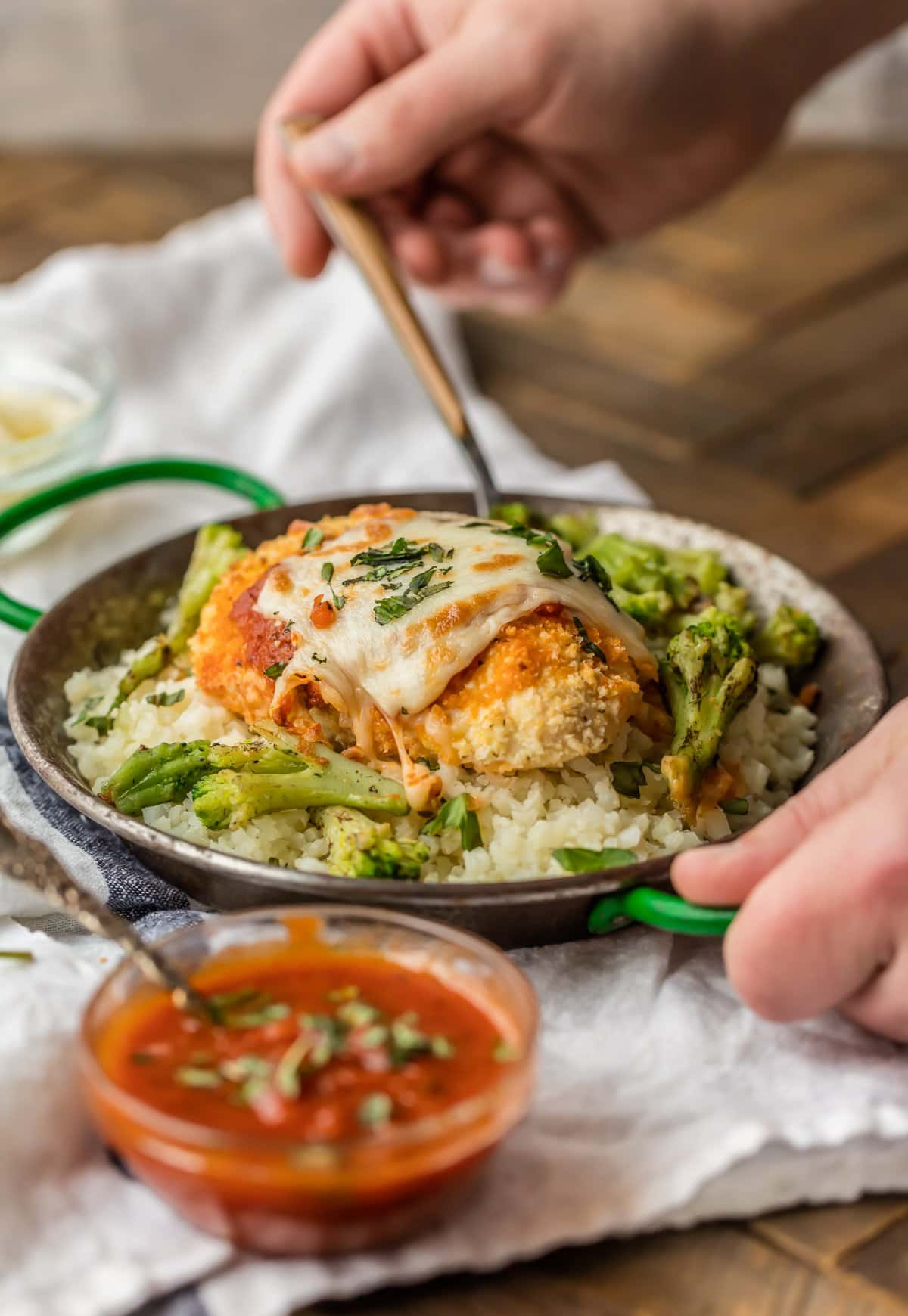 A bowl filled with cauliflower rice and baked chicken parmesan