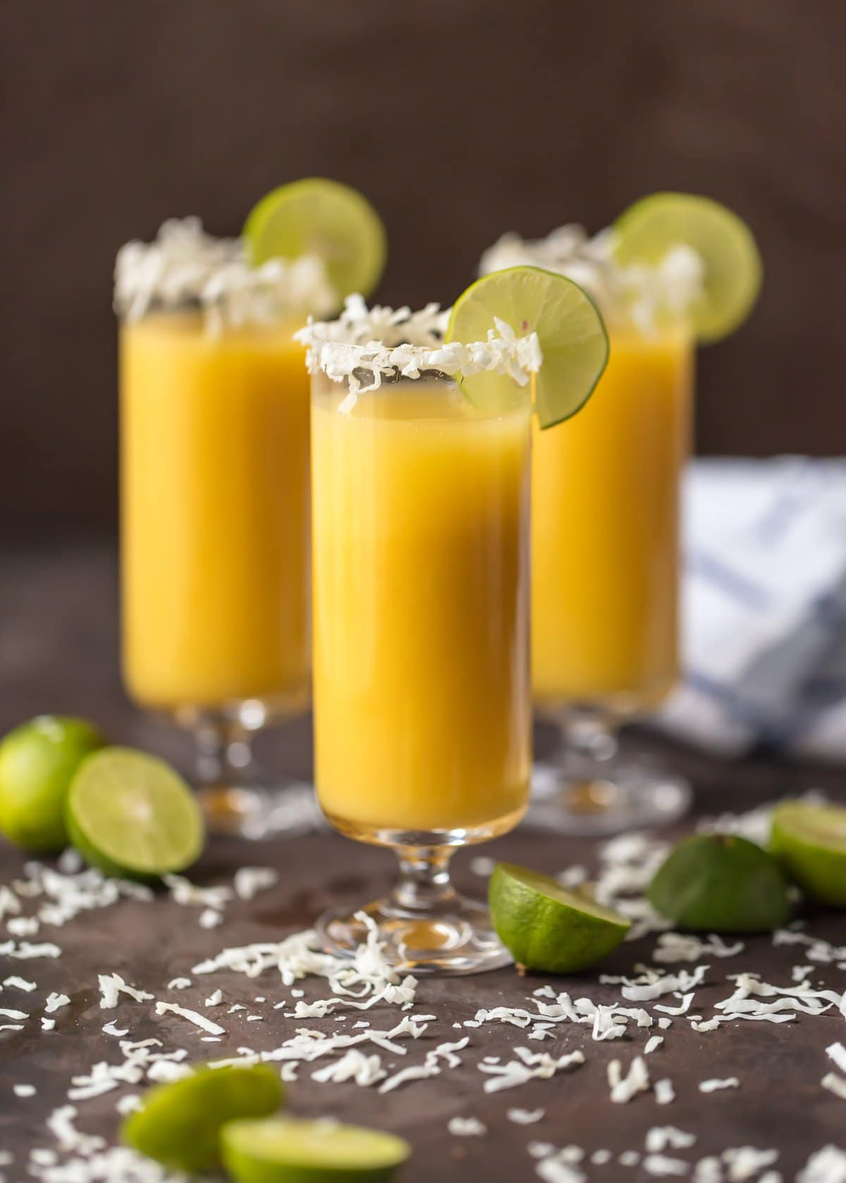 These TROPICAL MIMOSAS are the perfect year round sip! Made with coconut simple syrup, orange, mango, and pineapple juice, and of course champagne. SO TASTY!