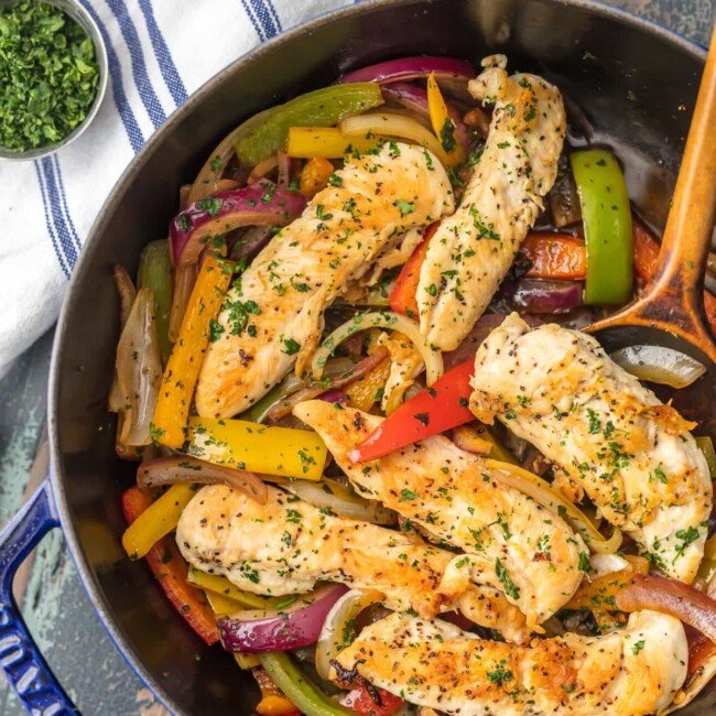 cilantro chicken stir fry in a skillet with a wooden spoon