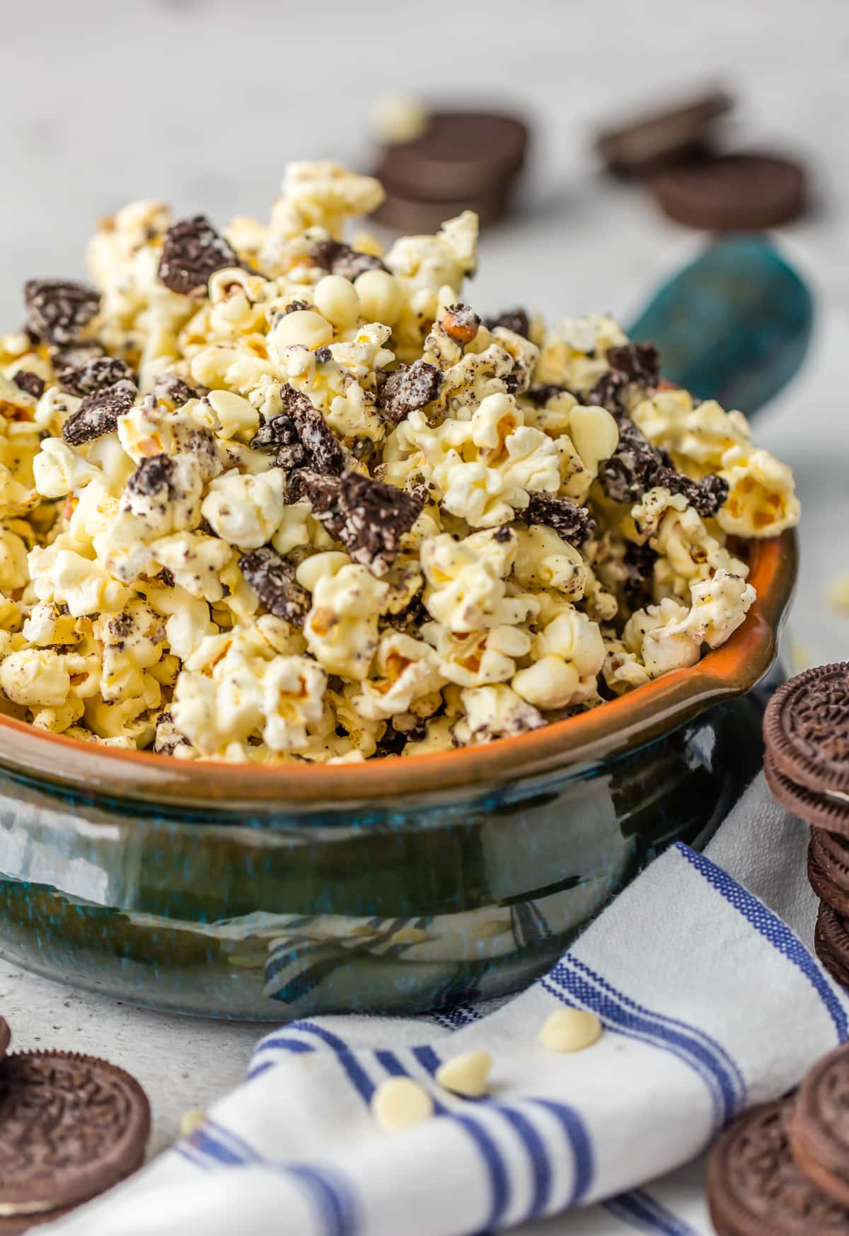 A bowl of Oreo and white chocolate popcorn surrounded by Oreos