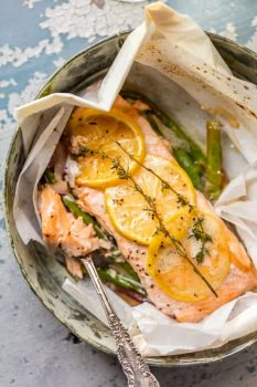 This LEMON BUTTER SALMON IN PARCHMENT is our favorite way to cook a healthy and delicious seafood meal at home! Asparagus and onion topped with succulent salmon, lemons, and thyme, and drizzled in lemon butter. SO EASY and amazingly good!
