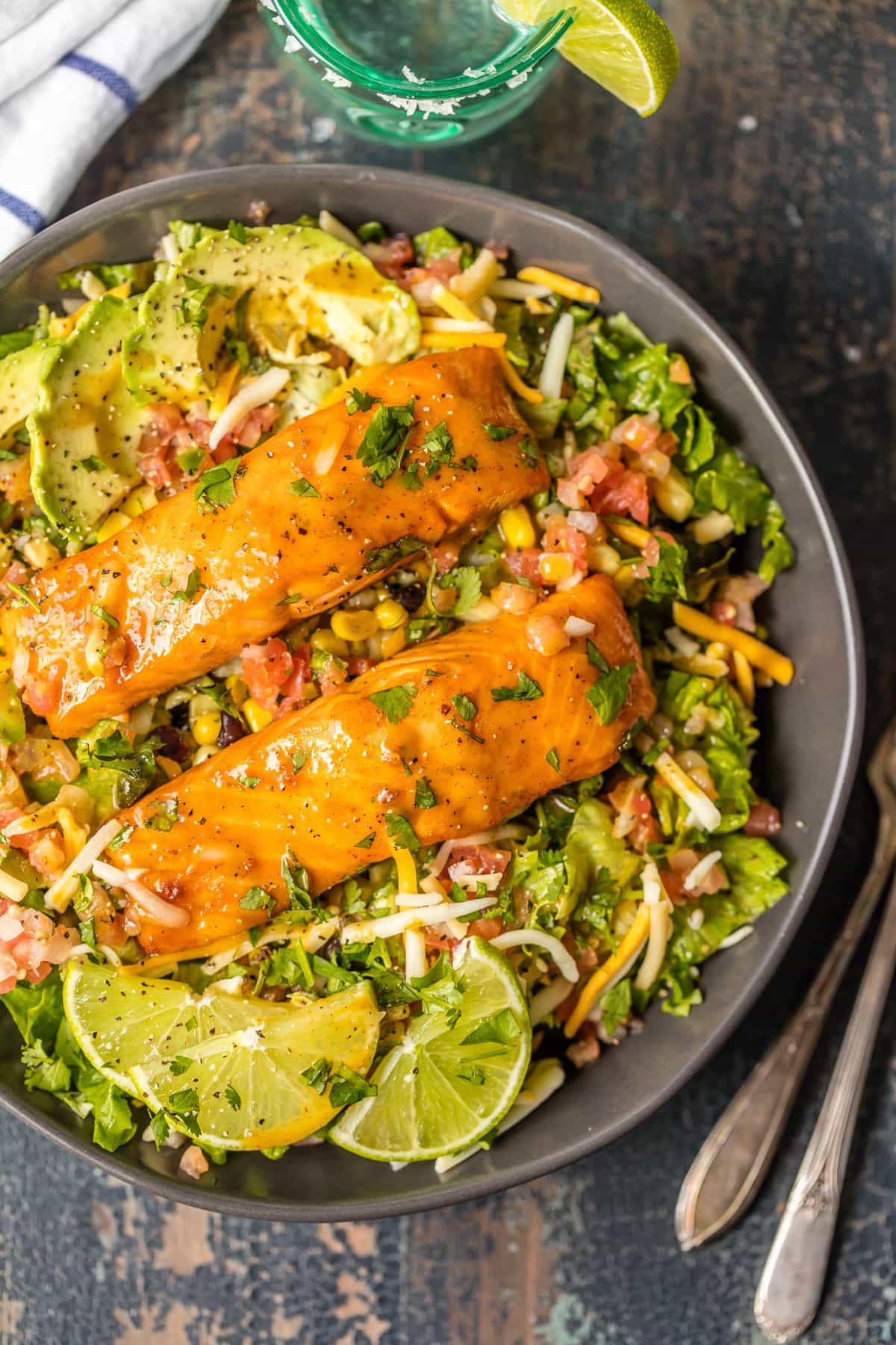 Large salad filled with avocado, lettuce, corn, black beans and topped with tequila lime salmon