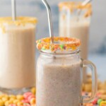 three smoothies in glasses surrounded by cereal