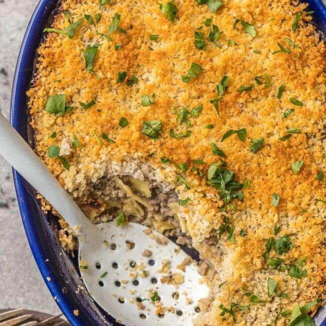 serving spoon inside blue baking dish with beef stroganoff casserole
