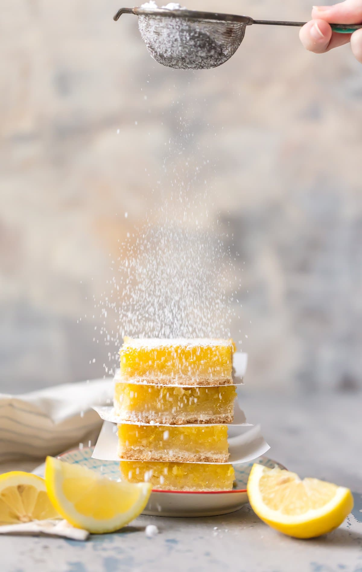 sprinkling powdered sugar on gluten free lemon bars