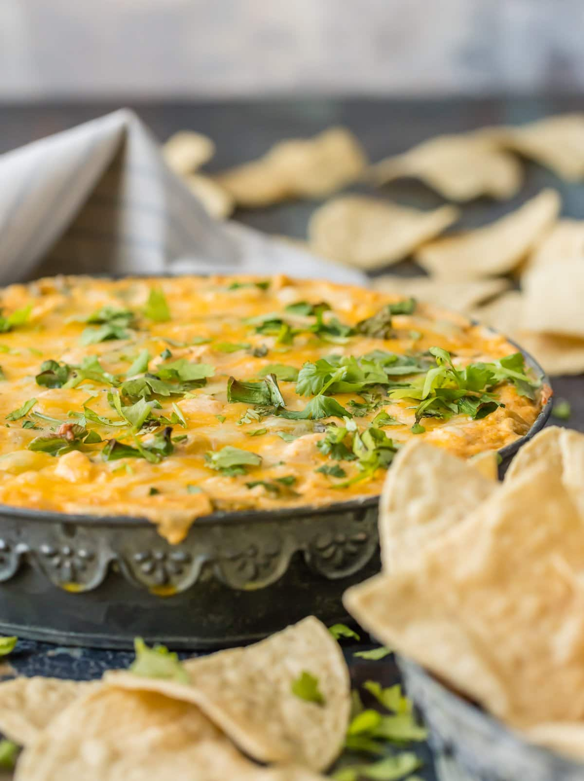 Large bowl of chicken enchilada dip surrounded by tortilla chips
