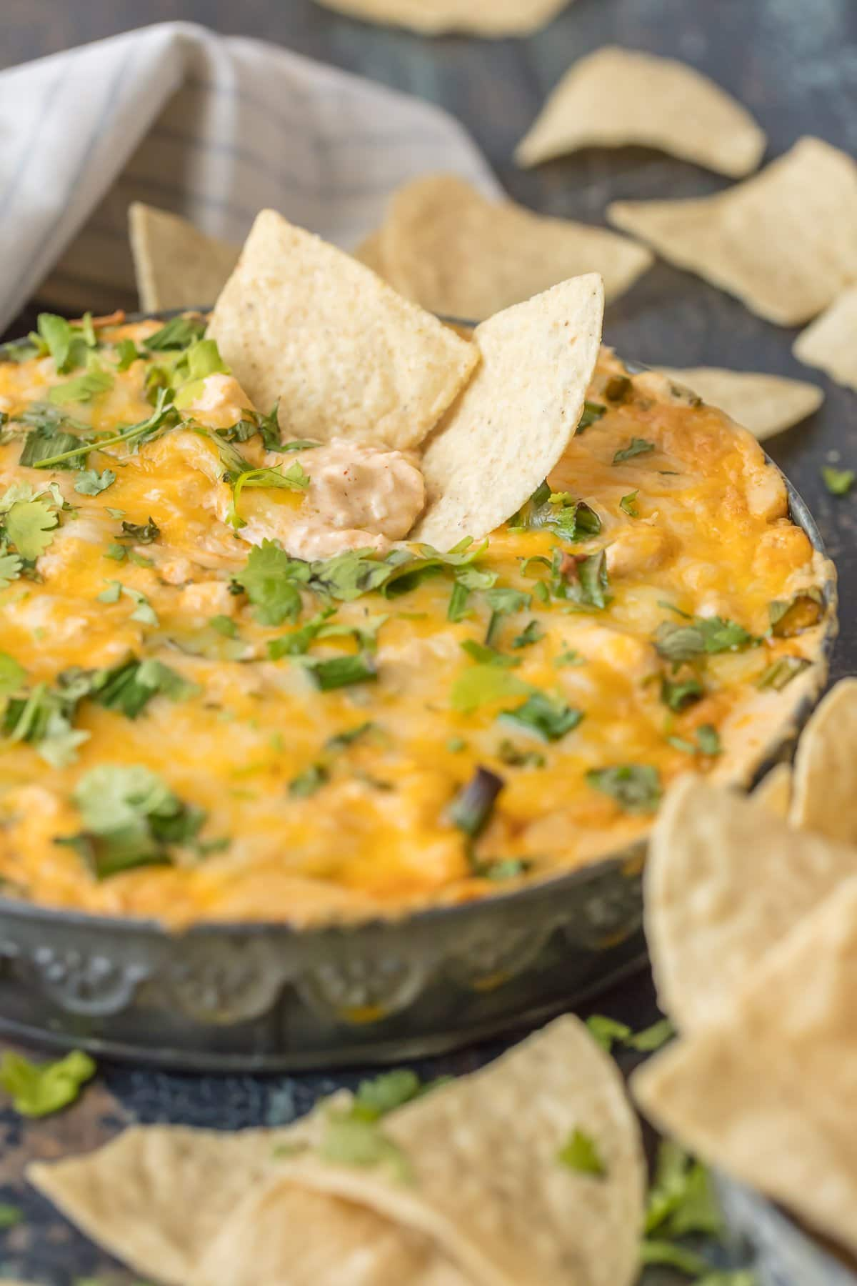 Two tortilla chips dipped into green chile dip