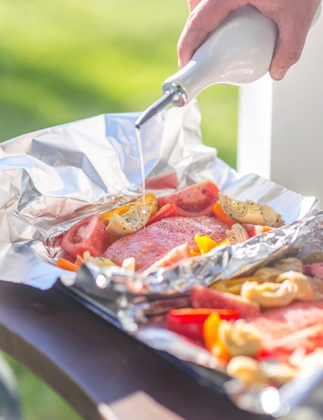These GRILLED CAESAR SALMON FOIL PACKETS are the perfect way to enjoy seafood on the grill this Summer. Salmon, tomatoes, artichokes, and sweet pepper in foil...easiest most delicious dinner ever.