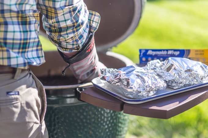 Grill foil packets next to a grill