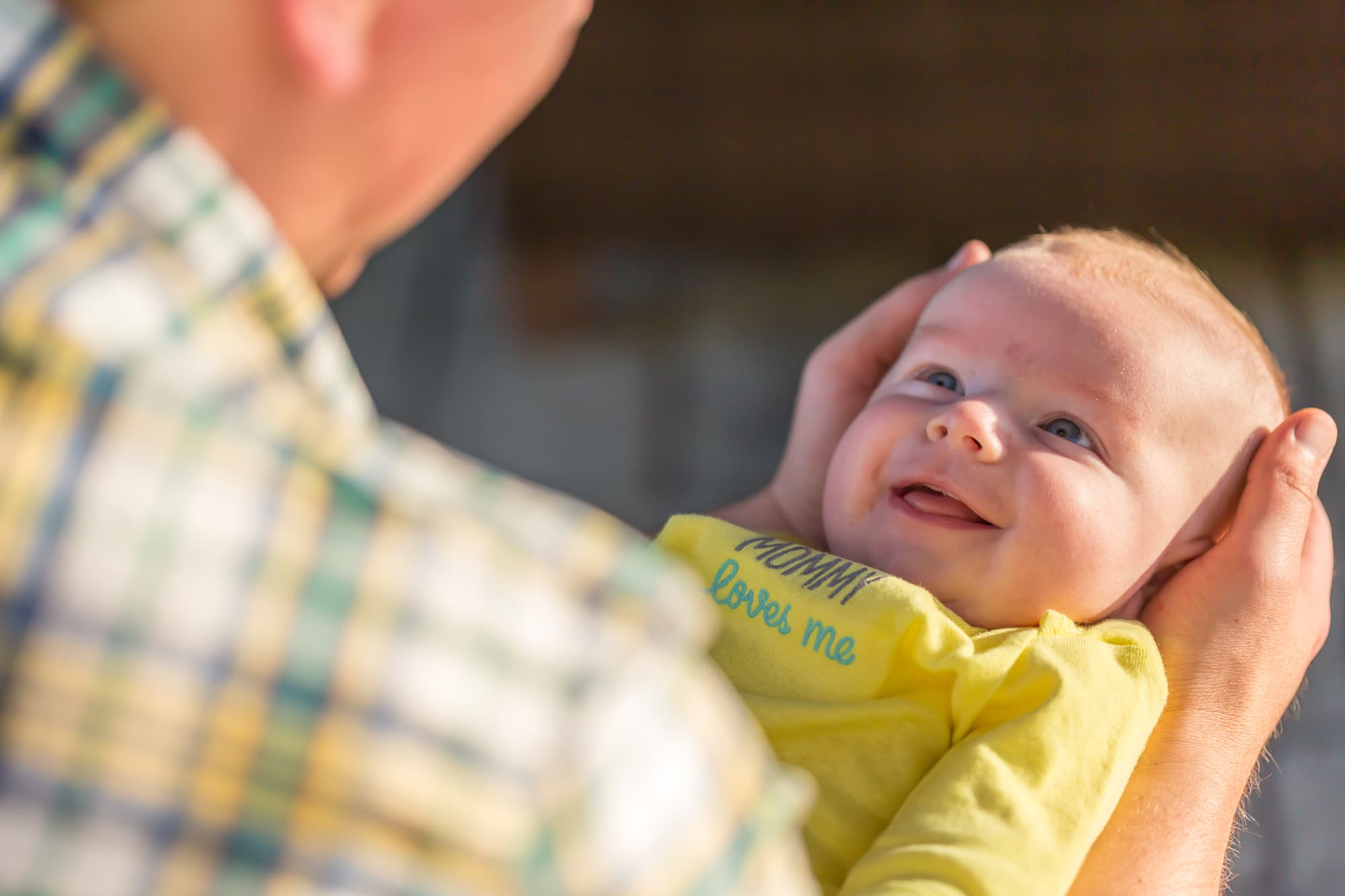 baby in yellow onesie smiling up at father