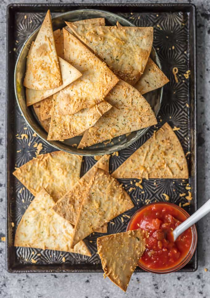 Homemade Tortilla Chips with Garlic Parmesan are a delicious and easy snack you can bake for Cinco de Mayo! It's so easy to make these Baked Tortilla Chips, and they're healthier and tastier than store bought! They're the easiest and most flavorful way to elevate chips and salsa.