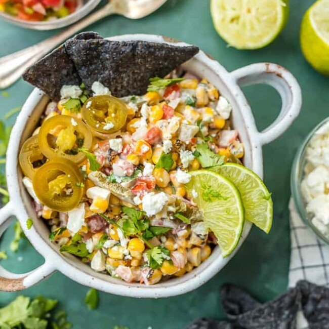 This MEXICAN STREET CORN SALSA recipe is my favorite spicy corn dip, just perfect for every occasion! Roasted corn, feta, lime juice, sour cream, cilantro, pico de gallo, and more!