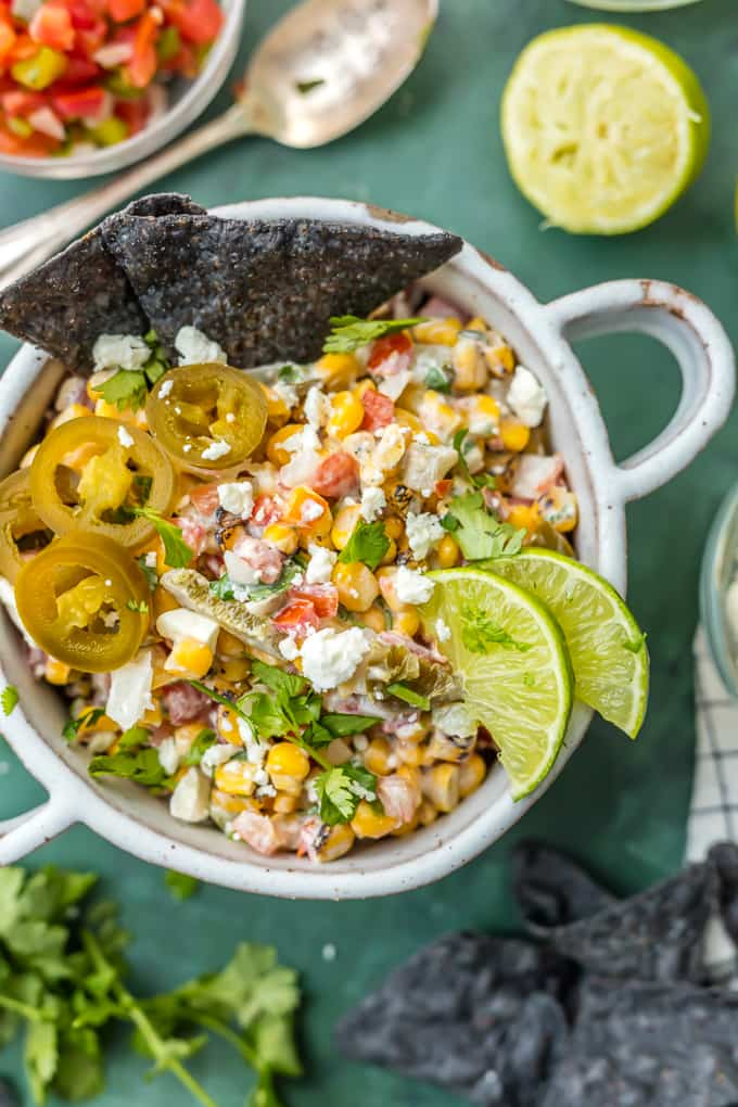 A bowl of Mexican street corn salsa with blue tortilla chips dipped in