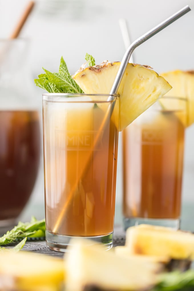 A glass of iced tea with a straw and a pineapple slice