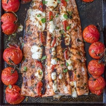 This Caprese Stuffed Salmon recipe is cheesy, delicious, and made on one pan! Baked salmon stuffed with tomato & mozzarella, paired with balsamic tomatoes.