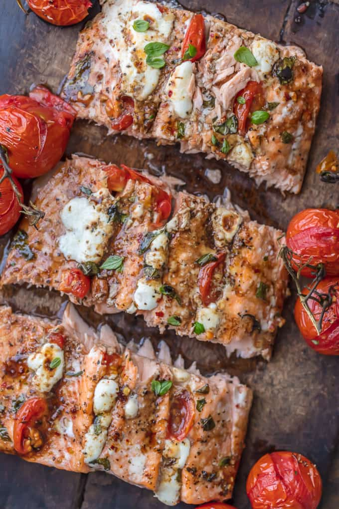 Caprese stuffed salmon on a wood board with roasted tomatoes