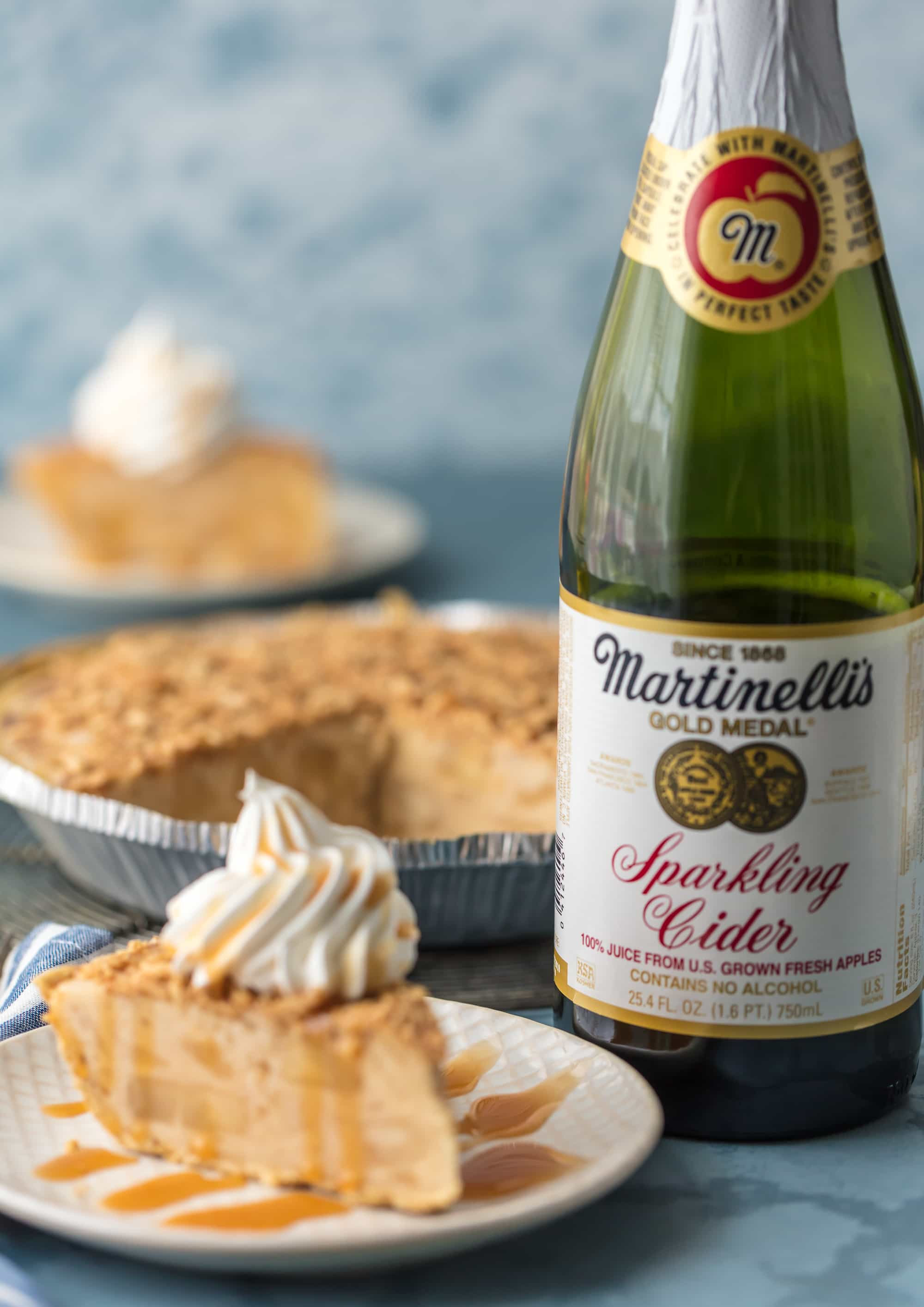 caramel apple freezer pie on plate topped with whipped cream with a bottle of martinelli's sparkling cider behind the plate