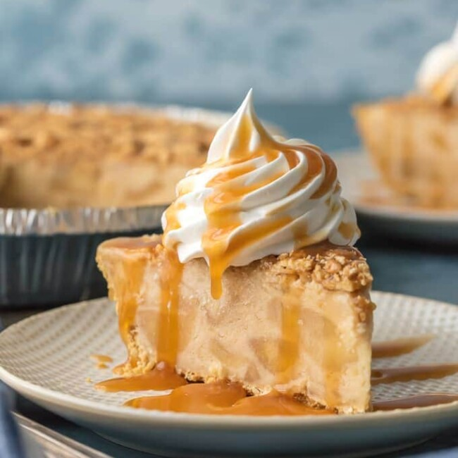 slice of pie on plate with whipped cream and caramel drizzled on top