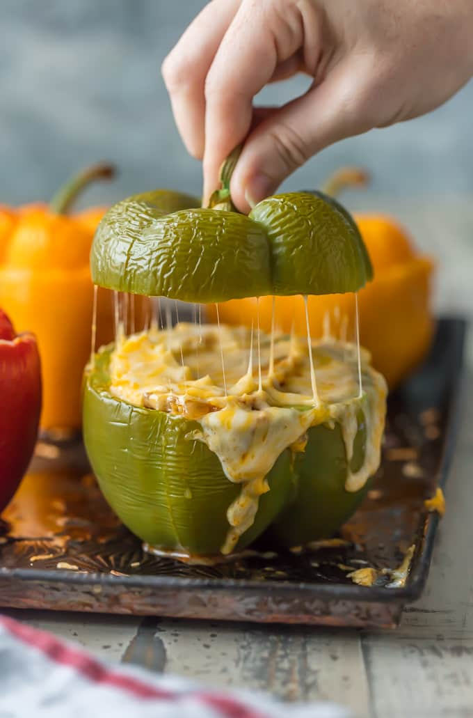 CHEESY ENCHILADA STUFFED PEPPERS are our go-to easy dinner recipe. These bell peppers are stuffed with beef, green chiles, onions, enchilada sauce, and so much cheese!