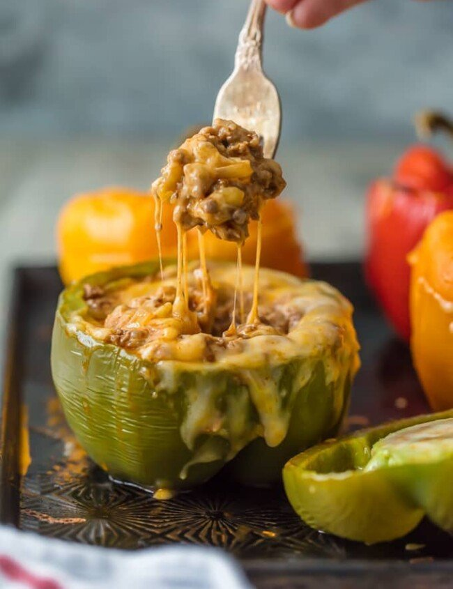 This STUFFED PEPPERS RECIPE is our go-to easy dinner recipe. These Cheesy Enchilada Stuffed Peppers are loaded with beef, green chiles, onions, enchilada sauce, and so much cheese! You won't believe how easy these are and how much your entire family will love them.
