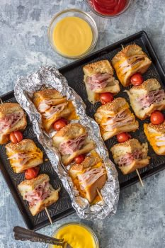 These Cheesy Garlic Butter Sandwich Skewers are a twist on an old classic. Cheesy Ham, Turkey, and Roast Beef sandwiches drizzled with garlic butter and cooked to perfection in foil packets; such a fun and delicious lunch or dinner!